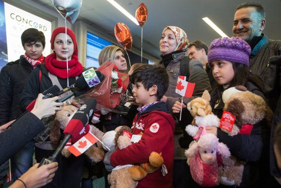Tima Kurdi, third from left, who lives in the Vancouver area, stands with her brother Mohammad Kurdi, top right, and his family, who escaped the war in Syria, upon arrival at Vancouver International Airport in Richmond, B.C., on Monday December 28, 2015. Pictured, from left to right, are Shergo Kurdi, 15, Haveen Kurdi, 16, Sherwan Kurdi, 5-months, being held by Tima, Rezan Kurdi, 8, their mom Ghousun Kurdi and Ranim Kurdi, front right, 10. Tima Kurdi's other brother Abdullah, whose young sons and wife died when their boat capsized during a desperate voyage from Turkey to Greece, abandoned his attempt to emigrate. THE CANADIAN PRESS/Darryl Dyck